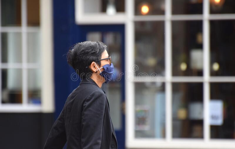 A woman wearing a face mask in public on the weekend that wearing face coverings became law in England stock photo