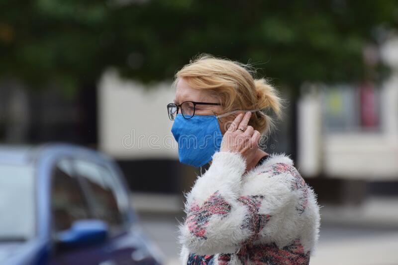 A woman in an English town centre wearing a face mask in public on the weekend that wearing face coverings became law in Englan royalty free stock images