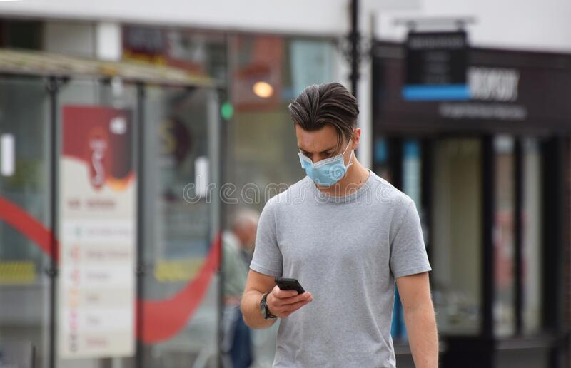 A young man texting on his phone wearing a face mask in public on the weekend that wearing face coverings became law in England royalty free stock photos