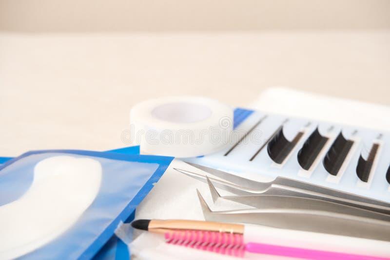 Wimper-Erweiterungs-Verfahrenshintergrund Werkzeuge Kleber, Pinzette, Bürsten Copyspace für Text - Schönheitssalon, -mode und -fr stockfotos