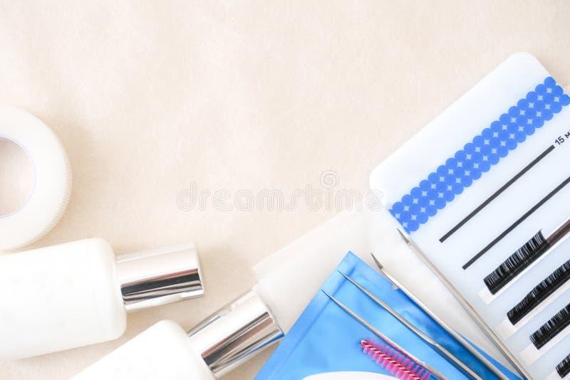 Wimper-Erweiterungs-Verfahrenshintergrund Werkzeuge Kleber, Pinzette, Bürsten Copyspace für Text - Schönheitssalon, -mode und -fr lizenzfreies stockfoto
