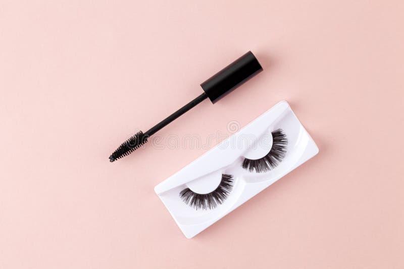 Wimpern für Frauen und Pinsel auf rosa Untergrund Obere Ansicht der Mascara-Bürste und lange falsche Striche Eyelash-Erweiterung stockfotografie