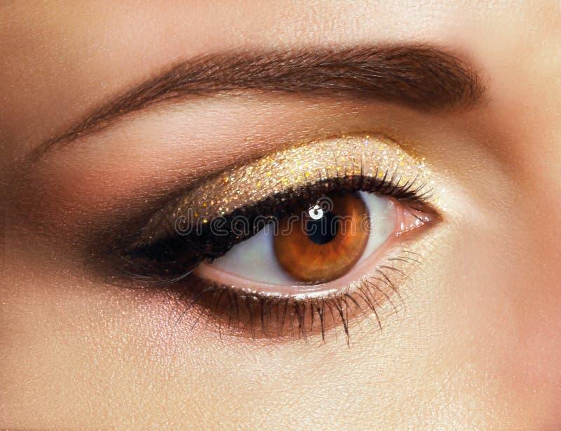 wimperntusche Schließen Sie herauf das Auge der Frau mit goldenem Lidschatten stockbilder