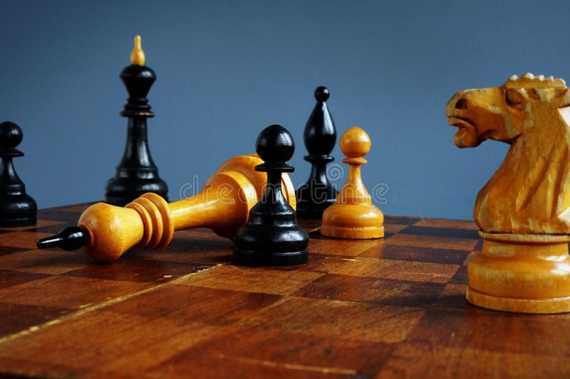 Win in business competition. Success in challenge. Pawn and king on chess board stock photo