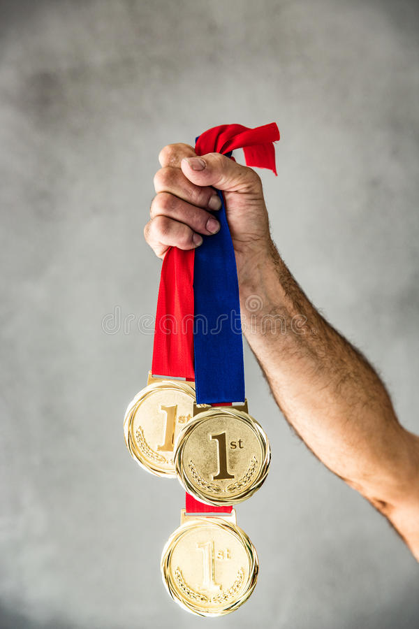 Win and success concept. Senior man holding medal in hand. Win and success concept stock images