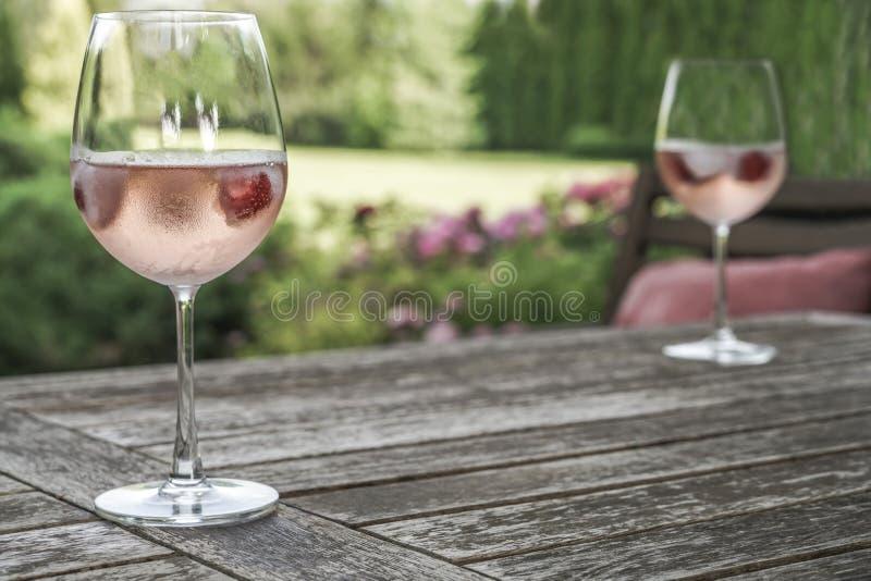 Win szkła na drewnianym stole przy ogródem obraz royalty free