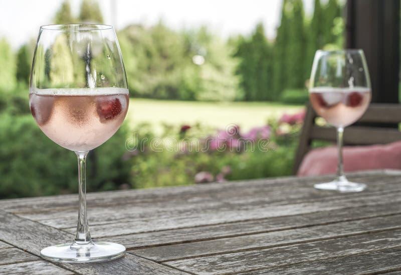 Win szkła na stole przy ogródem w słonecznym dniu zdjęcia stock