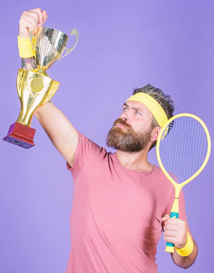 Win tennis game. Tennis match winner. Achieved top. Tennis player win championship. Athlete hold tennis racket and. Golden goblet. Man bearded hipster wear stock images