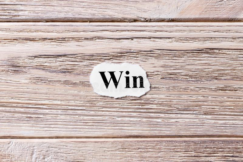 Win of the word on paper. concept. Words of Win on a wooden background royalty free stock photography