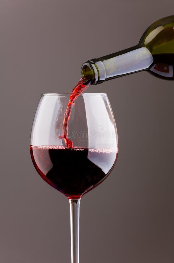 Wina dolewanie w szkle na popielatym tle zdjęcie royalty free