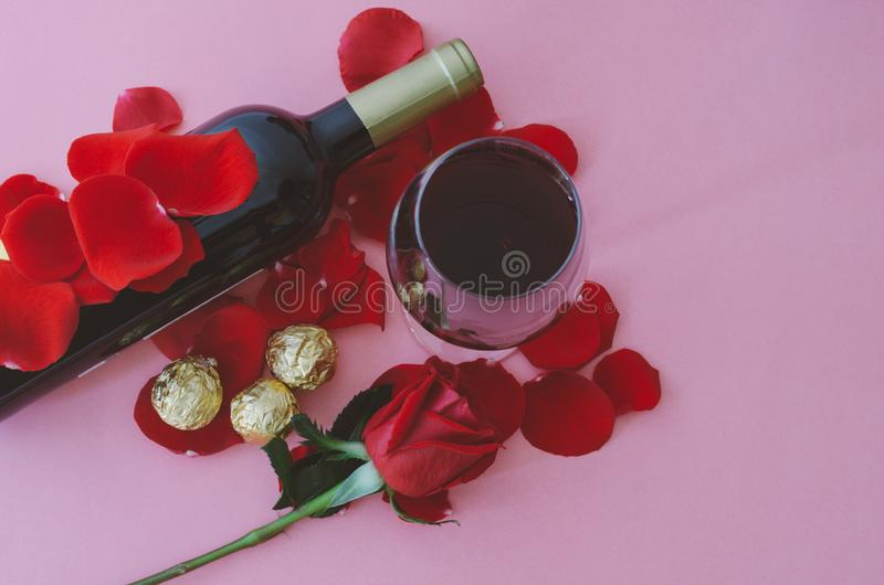 Wina szkło i czerwieni róża z czekoladami, na różowym tle to walentynki dni Odgórny widok obraz royalty free