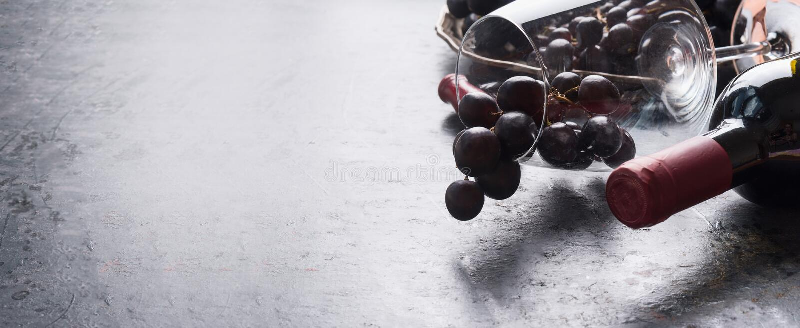 Wina szkło z czerwonego winogrona gronami, butelka wino na ciemnym tle, sztandar lub szablon, miejsce dla twój projekta obrazy stock