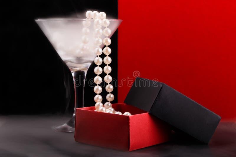 Wina szkło z mgłą i perl koraliki spada w rozpieczętowanego papierowego giftbox na mgłowej glansowanej powierzchni obrazy stock