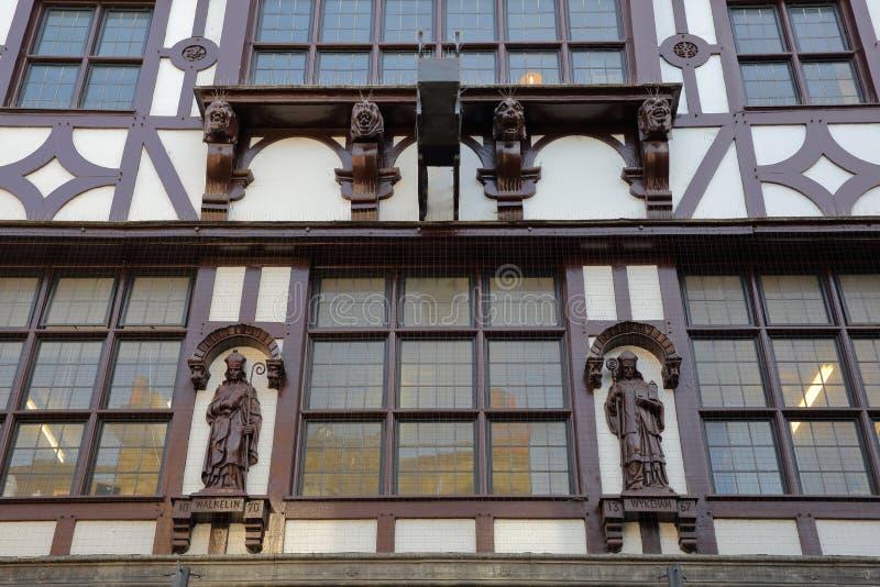 WINCHESTER, HET UK - 4 FEBRUARI, 2017: Buitenvoorgevel met houten standbeelden in de bezige en commerciële Hoofdstraat royalty-vrije stock afbeelding