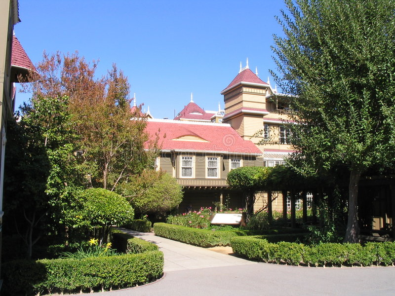 Winchester Mansion - San Jose. The facade of Winchester Mansion in San Jose, California with windows, the red roof, trees and the cars entrance stock image