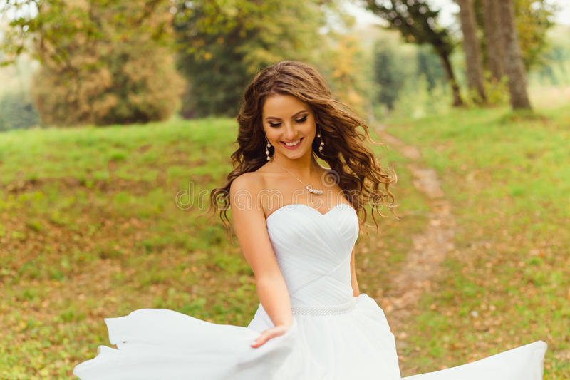 Wind blows bride& x27;s hair while she whirls her magnificent dress royalty free stock images