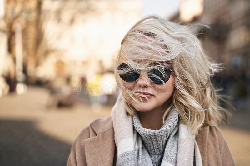 Wind blows lady`s blonde hair and covers her face and sunglasses royalty free stock photo