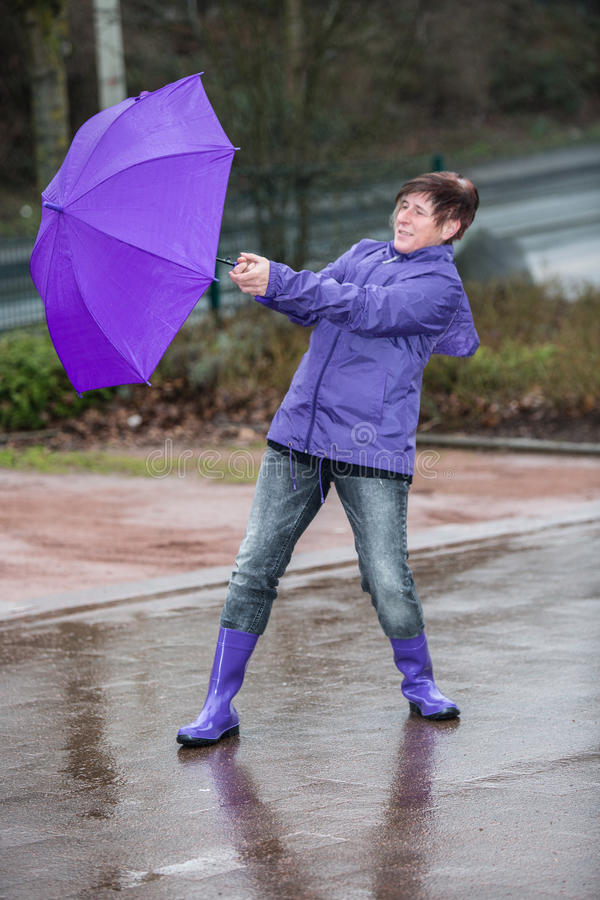 Wind blows the womans umbrella away stock photography