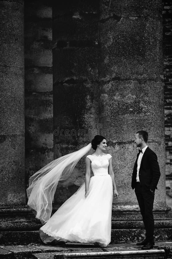Wind brennt Braut ` s Schleier durch, während sie mit einem Bräutigam zwischen Th steht stockfotografie
