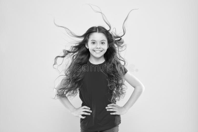 Wind can also damage hair. Girl adorable kid long wavy hair yellow background. Things you doing to damage your hair stock photos