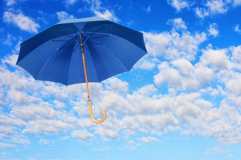 Wind of change concept.Blue umbrella flies in sky against of white clouds. royalty free stock photography