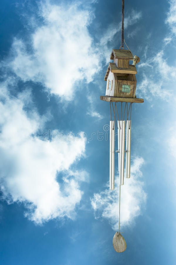Wind chime with blue sky and clouds in backgrounds. Wind chime (soft focus) with blue sky and clouds in backgrounds royalty free stock photo