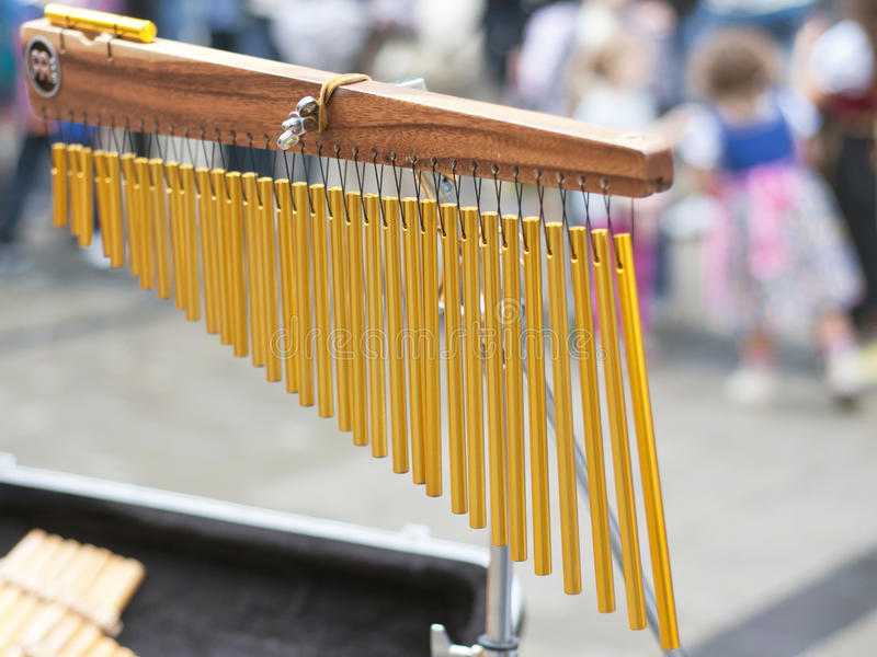 Wind chime pipes with croud in background.  stock photography