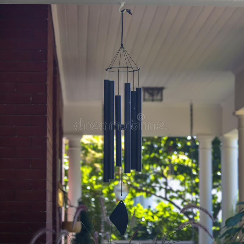 Wind chime on a red brick house with white pillars. Close up view of a blue wind chime hanging on the porch of a house on a sunny day. The house also has red royalty free stock photos