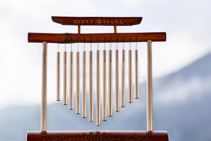 Wind chime with a wooden support. In front of a mountain profile royalty free stock images