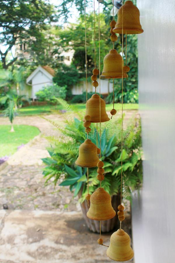 Wind chimes outside a cottage hanging on the porch. In the shape of bells, the chimes are ceramic with an apricot color stock photo