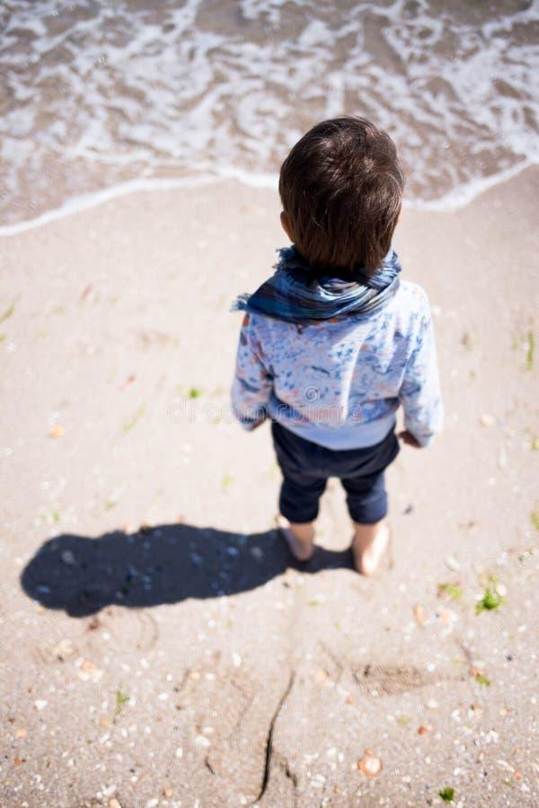 Wind, der das Haar und den Schal des kleinen Jungen durchbrennt stockfotos