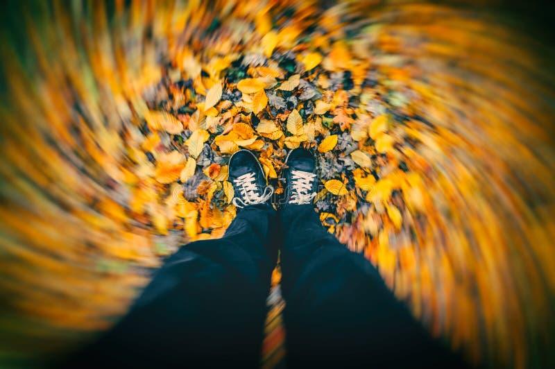 Wind die rond de mens blazen die zich op droge de herfstbladeren bevinden stock fotografie