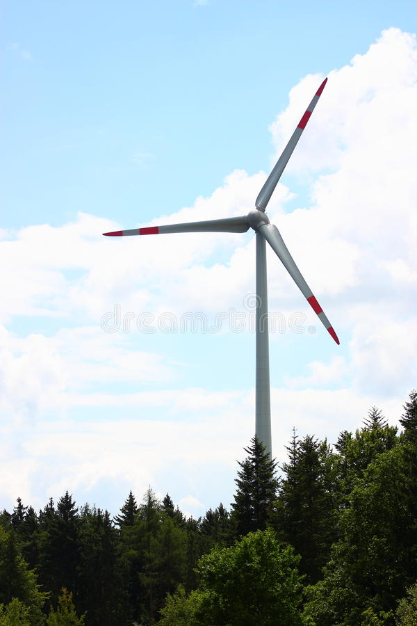 Wind energy. Modern wind mill, energy generator with green forest stock photography