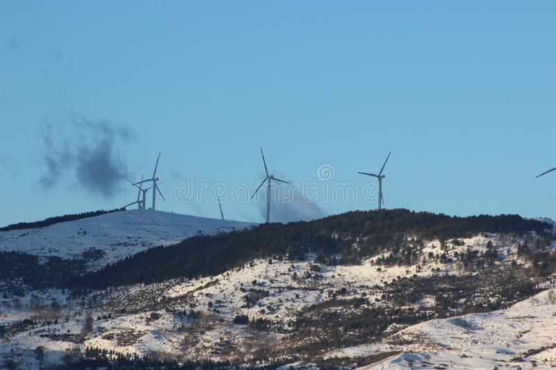 Wind energy, eco-friendly way to produce energy. Windmill and blue sky royalty free stock photos