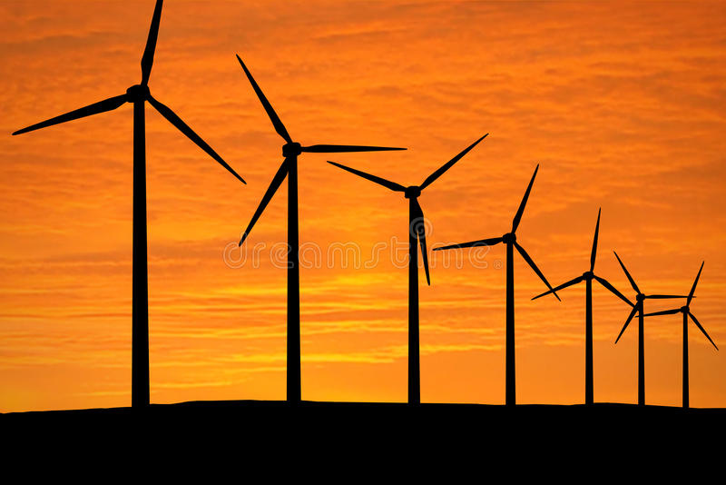 Wind Energy. Wind Turbines in front of a Sunset. Focus on the Silhouette royalty free stock photo