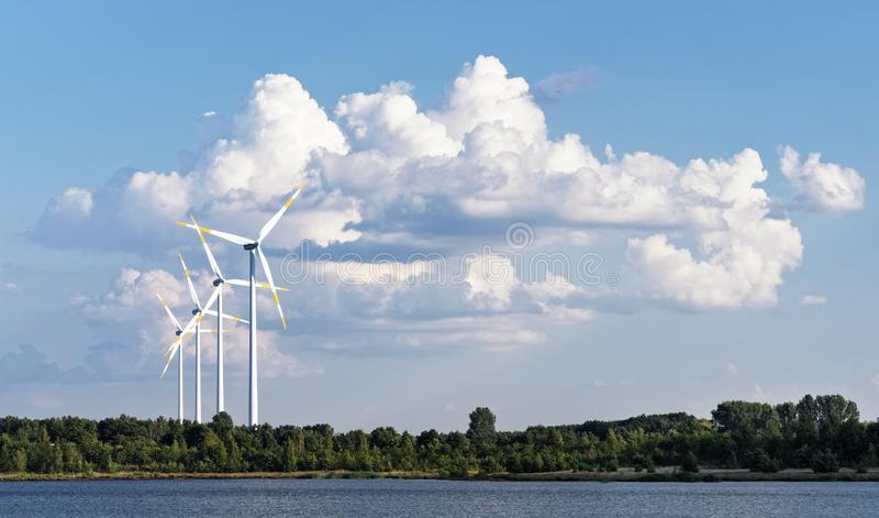 Wind energy - wind turbines in front of a cloud formation. Several wind turbines stand in front of a huge cloud formation at the shore of a lake, warm summer stock images