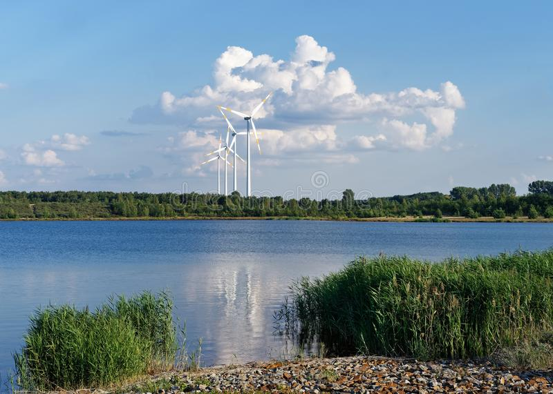 Wind energy - wind turbines in front of a cloud formation. Several wind turbines stand in front of a huge cloud formation at the shore of a lake, warm summer stock photography
