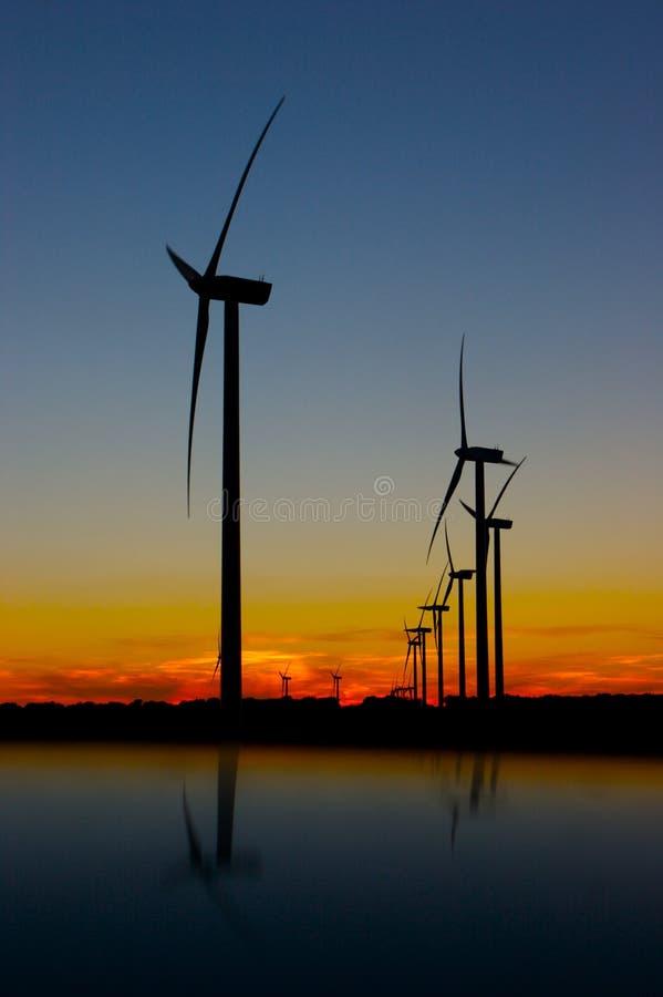 Wind farm at dusk. With trees in shadows stock photos