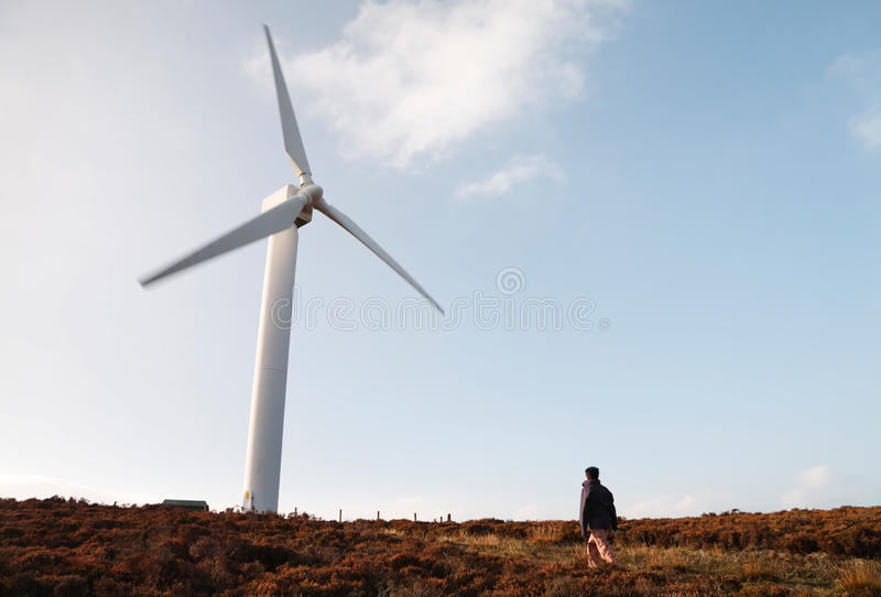 Wind farm and hiker. A woman hiker walks towards a wind farm in British countryside royalty free stock photos