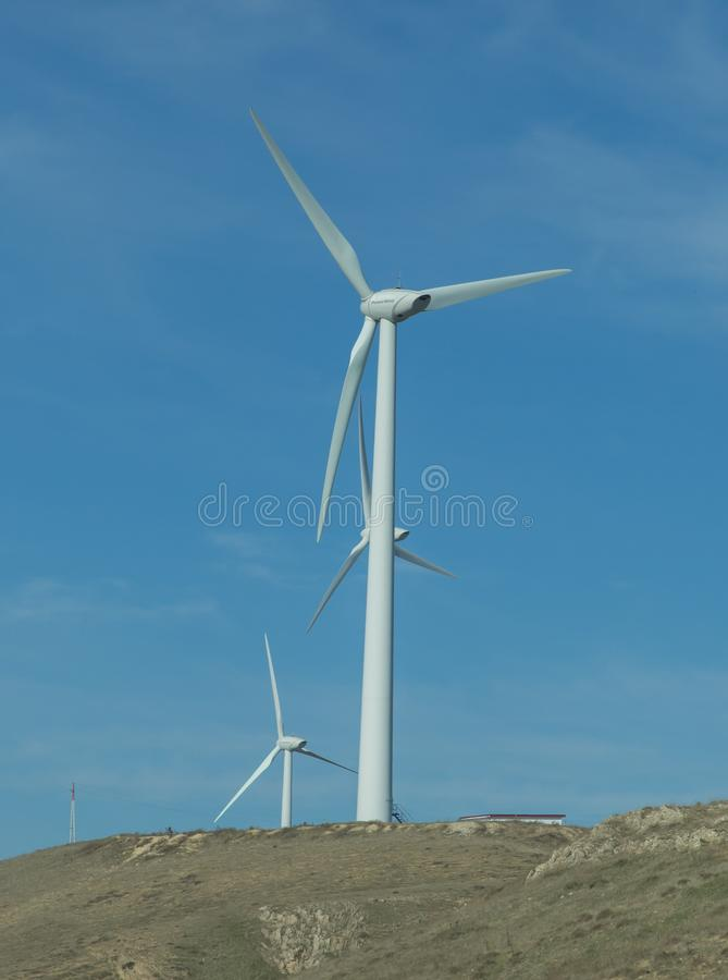 Wind farm: Industrial Eolic installation . Wind turbines towers again cloud blue sky on a wind farm sustainable, renewable energy royalty free stock photos