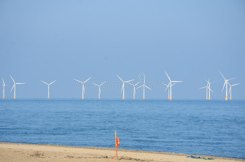 Wind farm with sandy beach and lifebelt. In foreground royalty free stock photos