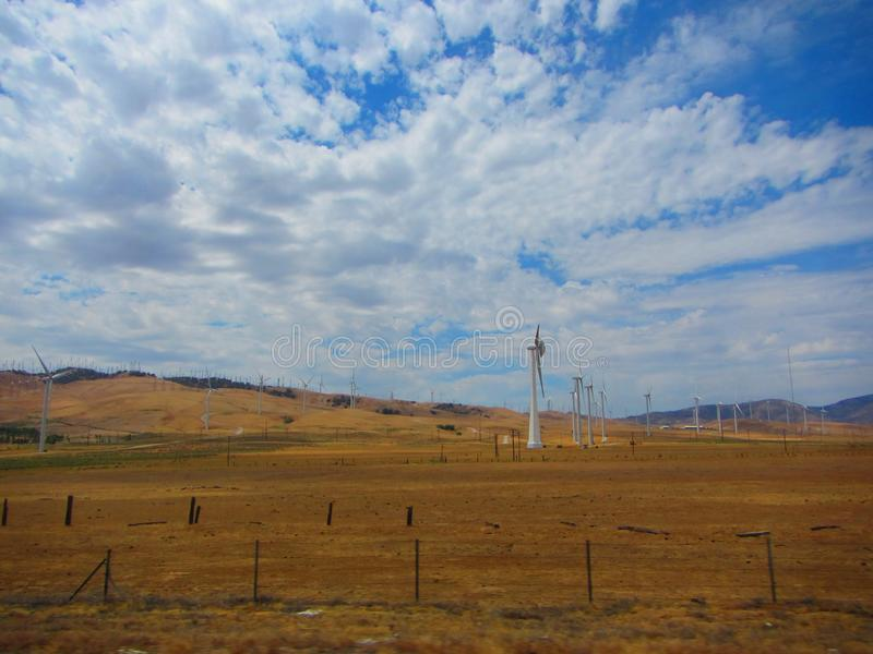 Wind farm, view of hundreds of wind trubines in mountainous fields in California. Example of sustainable energy, fighting global warming or climate change royalty free stock photo