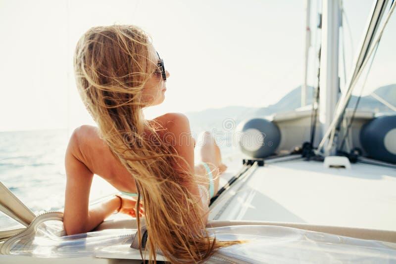 Wind in het meisjeszeilen van haarzeilen op zeilboot stock afbeelding