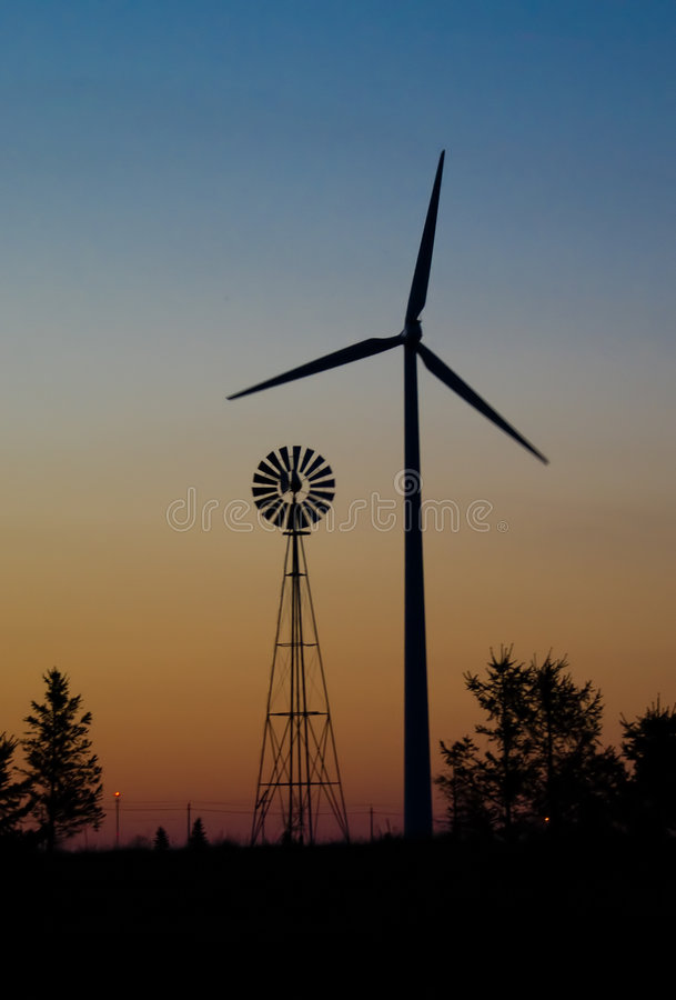 Wind Mill Generations. Sunset of Wind Mills just outside Rochester, Minnesota. Both Modern and old style of Wind mills royalty free stock image