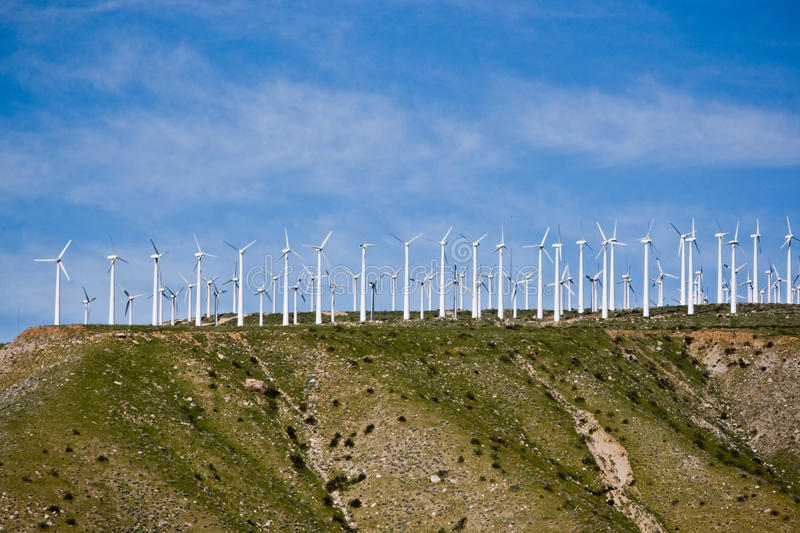 Wind Mill Turbines. Farm of wind turbines with the sky and clouds in the background stock photography