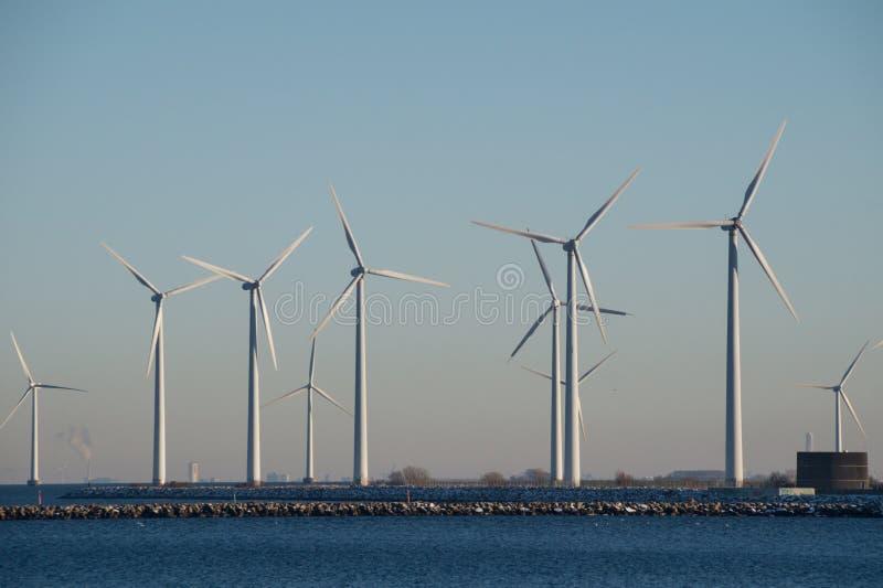 Wind mills, Copenhagen Harbour, Denmark. Onshore and offshore wind mills in Copenhagen Harbour, Denmark producing sustainable energy royalty free stock image