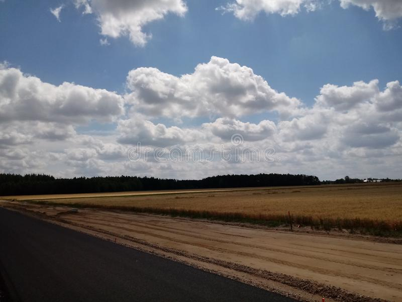 The wind in the new road. The wind that sways wheat in the field. Blue sky whit clouds. Construction of a new asphalt road among wild nature stock photography