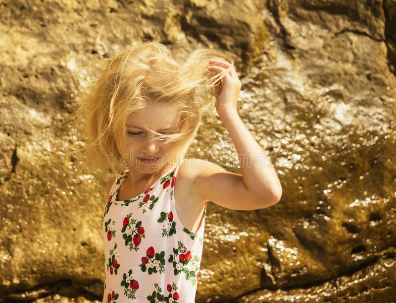 The wind is playing the hair in blond  girl on the beach royalty free stock images