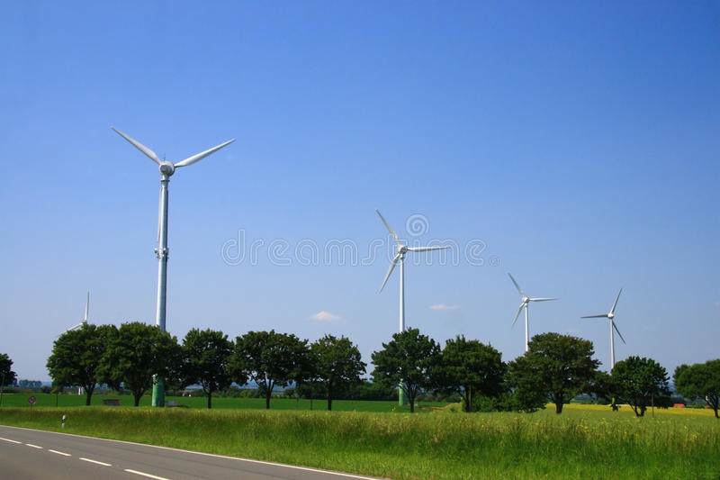 Wind power. Photo shows the brandnew wind energy machines in germany. blue sky little clouds and nice fields. a street besides the field stock photo