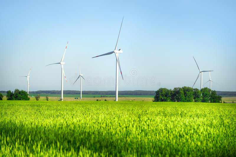 Wind power plant in the bright green field stock photo